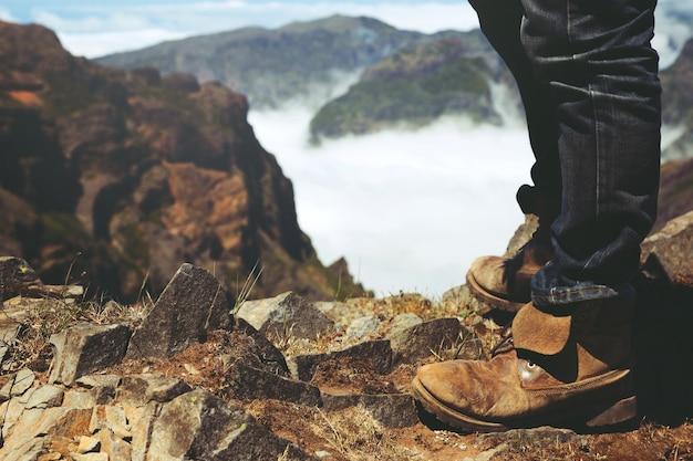 休んでいる旅行者。息を呑むような素晴らしい森の山の岩の景色を楽しみながら、高い山の頂上に立っています。