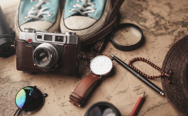 Traveler's accessories on old vintage map