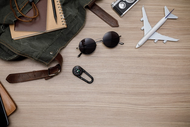 Traveler's accessories with passport, books of travel plan, wallet, camera, mobile phone, backpack and airplane toy on oak wooden table, flat lay with copy space, travel concept background