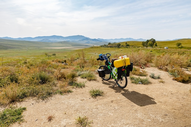 Traveler's bike with bags, landscape in mongolia, bike adventure travel, tourist bike