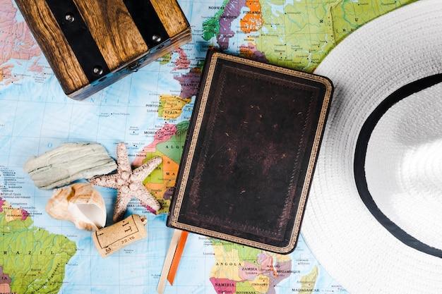 Diario del viaggiatore, conchiglia e cappello sulla mappa