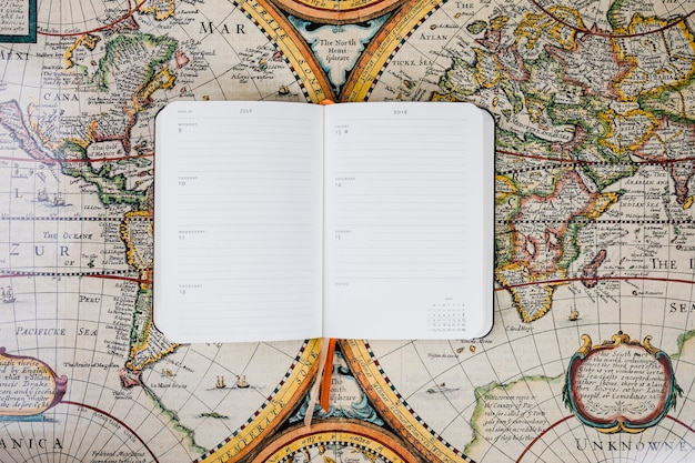 Traveler's empty diary on historical map
