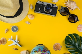 Traveler's equipments with seashell on yellow background