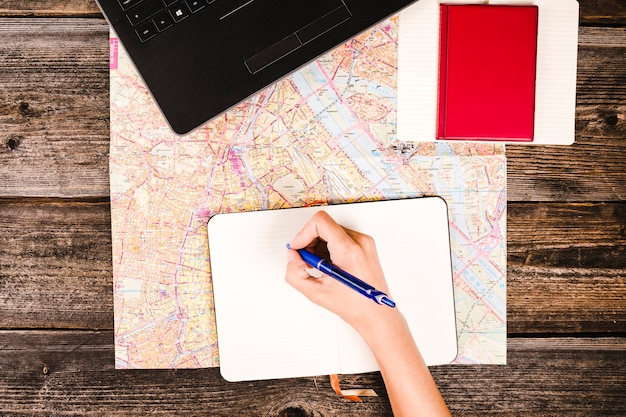 Traveler's hand writing on notepad over map