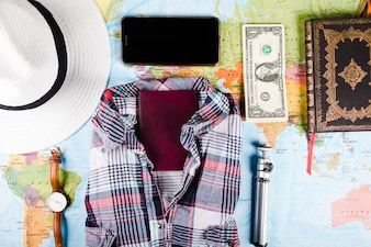 Traveler's shirt with banknotes, passport and accessories on map