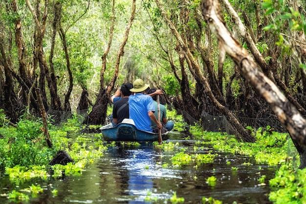 Путешественник осматривает традиционную лодку в лесу тра су, путешествие по дельте меконга, вьетнам