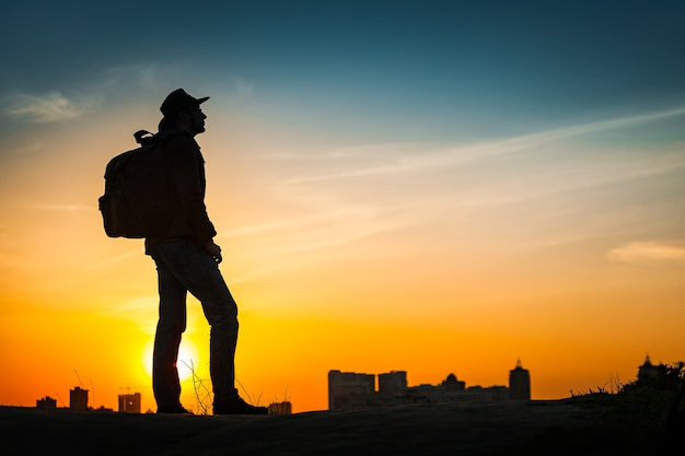 놀라운 일몰을 보고 있는 여행자 실루엣. 저녁 도시 풍경 위 언덕에 혼자 서 있는 배낭과 카우보이 모자와 젊은 캐주얼 남자. 라이프 스타일 여행 개념 야외 배경입니다. 키예프, 우크라이나