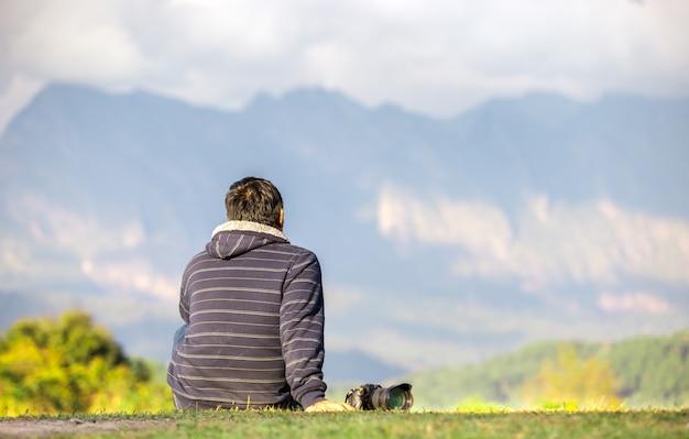 여행자는 아름 다운 관점에 그의 카메라와 함께 앉아