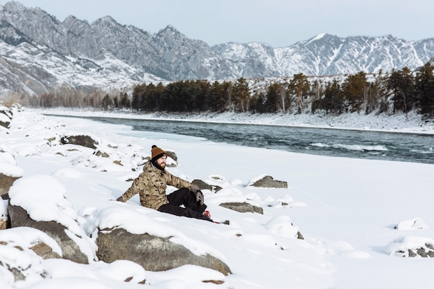 The traveler sits alone with nature on mountains and rivers in winter. the concept of travel and trips out of town.