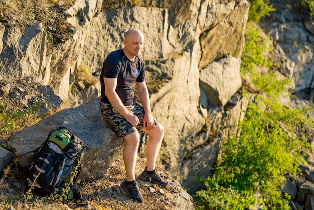 A traveler sits on a stone with a backpack near his legs