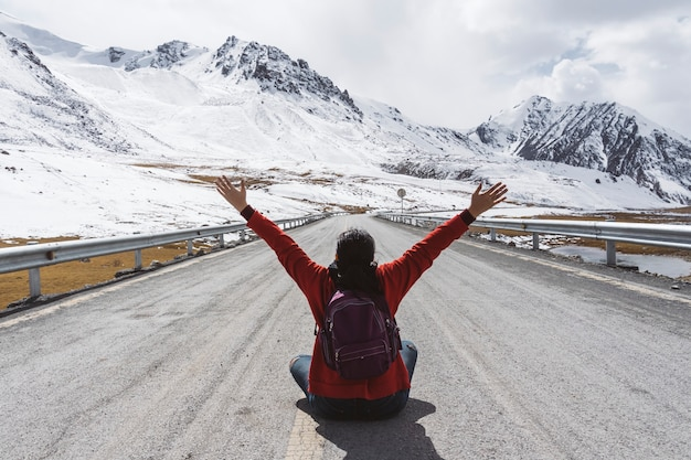 Traveler sitting and raising arms at the karakoram highway