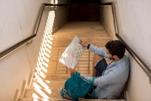 Traveler sitting on stairs and looking on map
