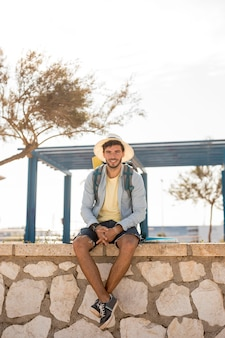 Traveler sitting on a stone fence