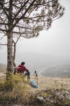 Traveler sitting next to a tree