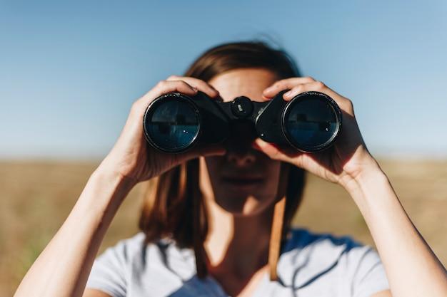 쌍안경을 통해 감시하는 여행자
