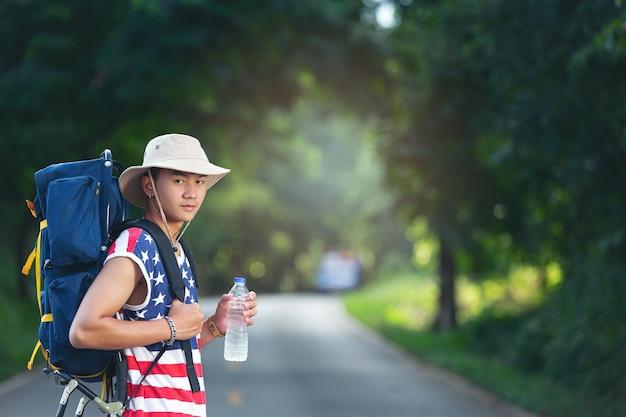 Путешественник стоит и держит бутылку питьевой воды на проселочной дороге