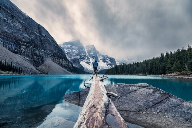 Traveler standing on log in maraine lake on gloomy day at banff national park