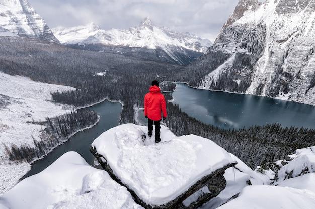 캐나다 요호 국립공원에서 눈이 내리는 오하라 호수가 있는 오파빈 고원의 바위 위에 서 있는 여행자