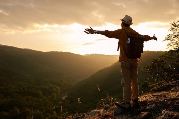 Путешественник стоит на краю обрыва и оглядывается на гору.