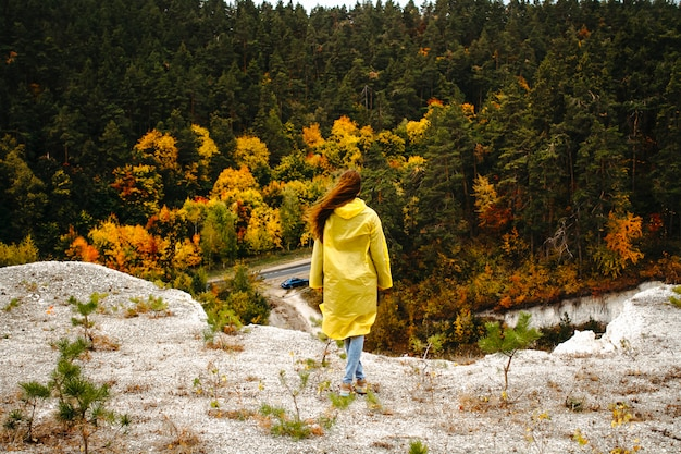 A traveler stands on the edge of a chalk mountain with his back to the frame in a yellow raincoat