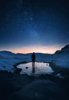 Путешественник стоит в секретном горячем источнике ночью в исландии под захватывающим дух звездным небом.
