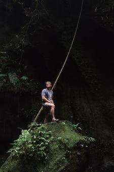 Путешественник стоит на краю замшелого камня в пещере бали индонезия
