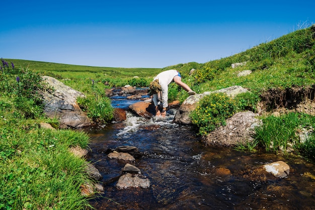 Traveler on stone in mountain creek. adventure of tourist. hiking in mountains. rich vegetation of highlands. stream of clear water in brook.
