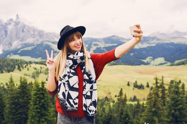 Стильная молодая женщина путешественника использует смартфон для самостоятельного фото в горах
