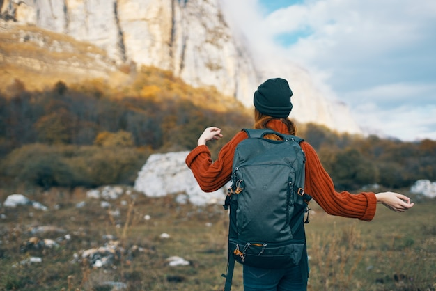 A traveler in a sweater and a hat is resting in the mountains in nature and a backpack on her back