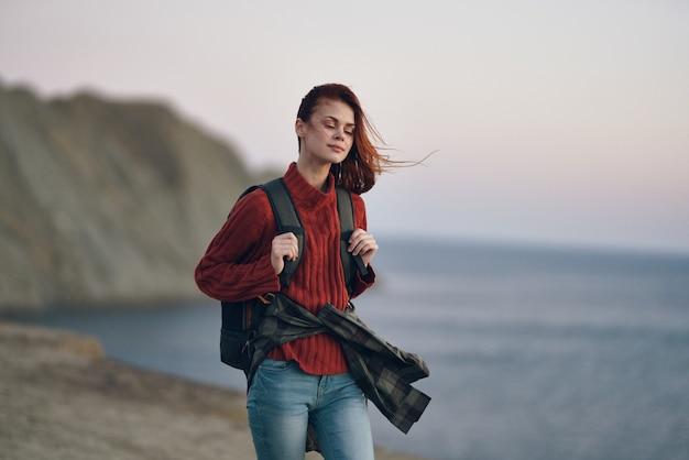 背中にバックパックと背景のビーチの海の山々と旅行者のセーター