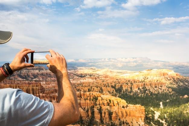 旅行者はモニュメントバレーで写真を撮ります。