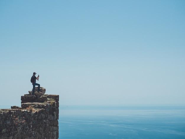 スマートフォンで素晴らしい海の景色の写真を撮る旅行者