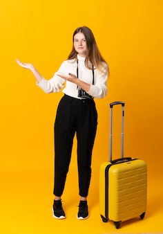 Traveler teenager girl with suitcase extending hands to the side for inviting to come