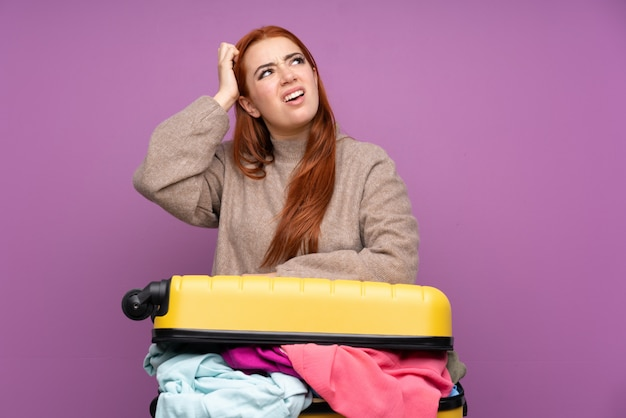 Traveler teenager woman with a suitcase full of clothes having doubts and with confuse face expression