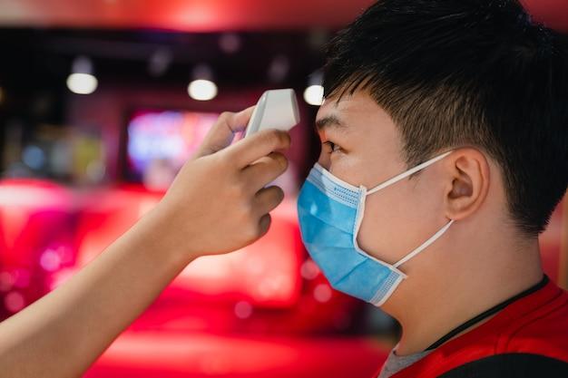 世界的なコロナウイルス(covid-19)の発生時の旅行者の体温チェック。フェイスマスクを身に着けているアジアの観光客の男性は熱チェックを持っています