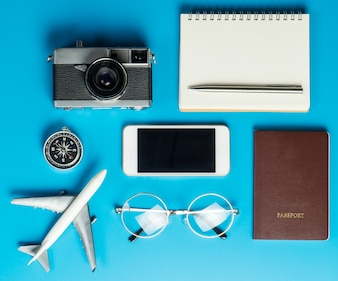 Traveler tools and documents flatlay on blue surface