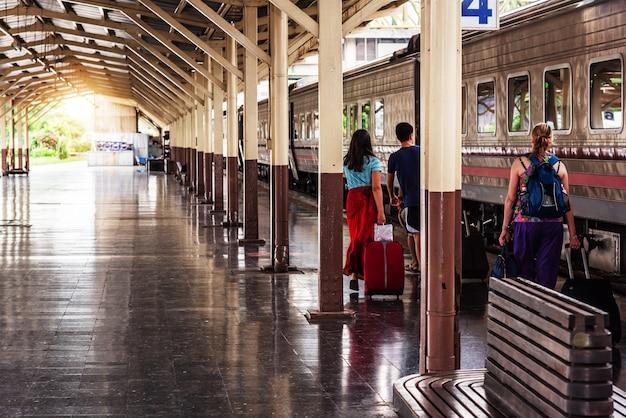 旅行者の観光客は、駅で電車に乗るために歩いて荷物を引きずっています