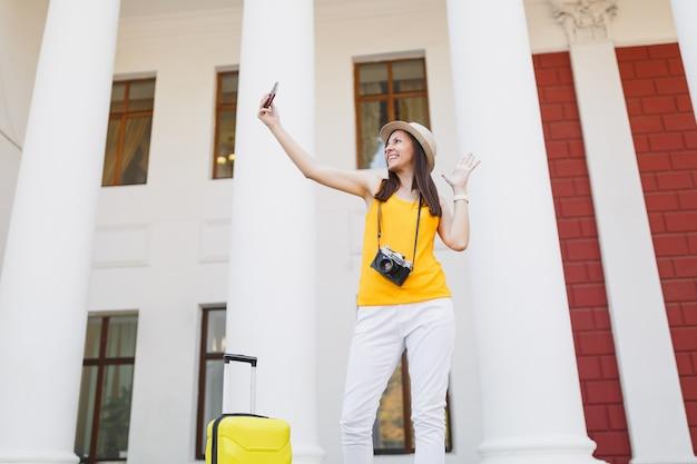 Путешественник турист женщина делает селфи выстрел, разговаривает по мобильному телефону, звонит другу, заказывает такси, отель на мобильном телефоне на открытом воздухе. девушка выезжает за границу на выходные. туризм путешествие образ жизни.