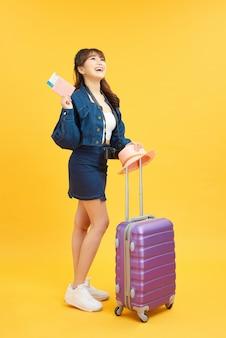 黄色のオレンジ色に分離された首にデジタルカメラと夏のカジュアルな服を着た旅行者観光客の女性