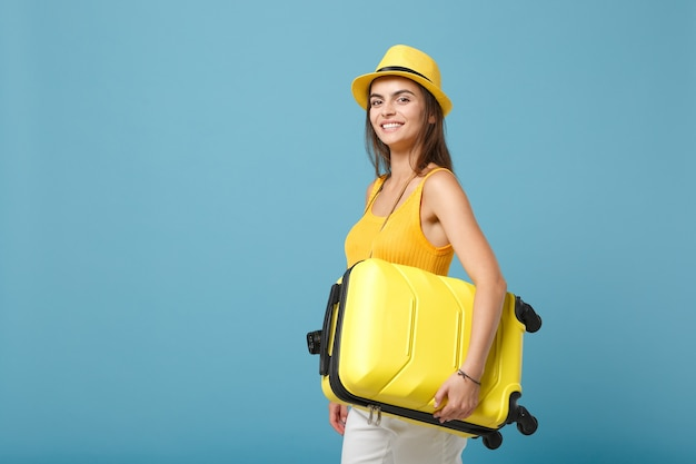 黄色のカジュアルな服を着た旅行者の観光客の女性、青いスーツケースの写真カメラと帽子