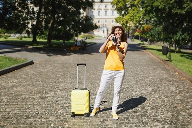 노란색 캐주얼 옷 모자를 쓴 여행자 관광 여성은 여행가방을 들고 복고풍 빈티지 사진 카메라 야외에서 사진을 찍고 있습니다. 주말 휴가를 여행하기 위해 해외로 여행하는 소녀. 관광 여행 라이프 스타일.