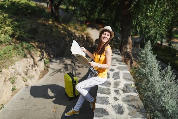 여행가방을 들고 노란색 옷 모자를 쓴 여행자 관광 여성은 도시 야외에서 돌 위에 앉아 옆을 바라보며 도시 지도를 들고 있습니다. 주말 휴가를 여행하기 위해 해외로 여행하는 소녀. 관광 여행 라이프 스타일.