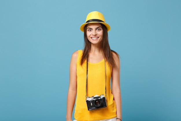 노란색 여름 캐주얼 옷, 파란색 벽에 고립 된 사진 카메라와 모자에 여행자 관광 여자. 주말 휴가 여행을 위해 해외로 여행하는 여성 승객. 항공 비행 여행 개념.