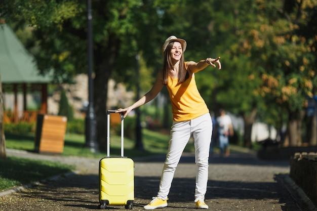 노란색 여름 캐주얼 옷을 입은 여행자 관광 여성, 여행 가방이 검지 손가락으로 도시 야외에서 걷고 있는 모자. 주말 휴가를 여행하기 위해 해외로 여행하는 소녀. 관광 여행 라이프 스타일.