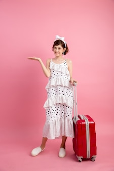 Traveler tourist woman in summer casual clothes with travel suitcase isolated on pink