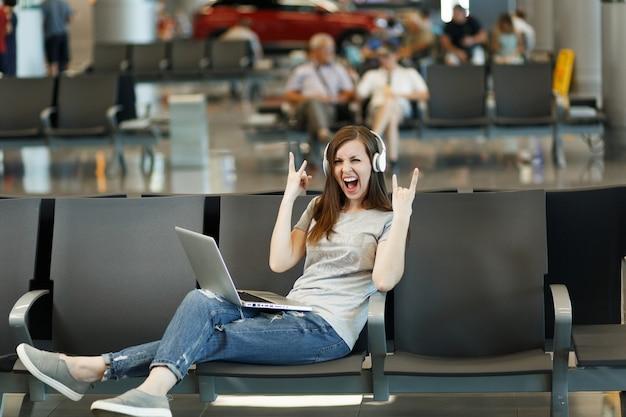 Женщина-путешественница с наушниками, слушающая музыку, работает на ноутбуке, показывая знак рок-нролла, ждет в холле вестибюля международного аэропорта