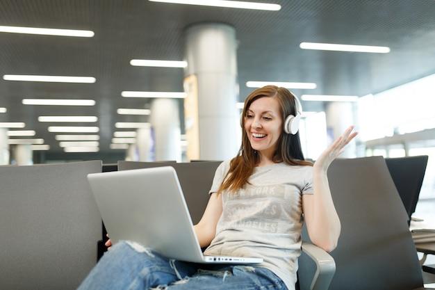Путешественник турист женщина с наушниками работает на ноутбуке, разводя руки во время видеозвонка, ожидая в холле вестибюля в аэропорту