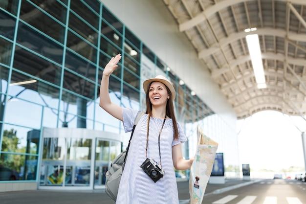 レトロなビンテージ写真カメラ、挨拶、友人との出会い、空港でタクシーに乗るために手を振る紙の地図を持つ旅行者の観光客の女性