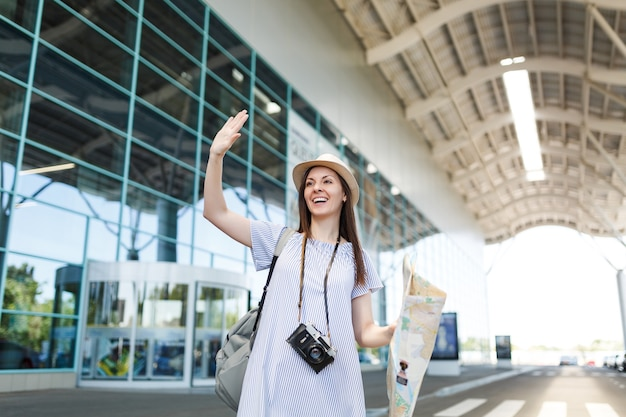 Traveler tourist woman with retro vintage photo camera, paper map waving hand for greeting, meeting friend and catch taxi at airport