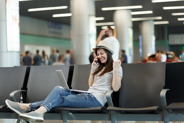 Путешественник-турист женщина, работающая на ноутбуке, разговаривает с жестом победителя по мобильному телефону, звонит другу, заказывает такси, ждет в холле в аэропорту